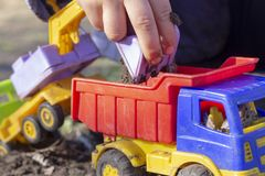 The child is playing in the street with sand; he loads the earth in an dump truck toy stock photo