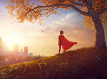Child is playing superhero. Little child is playing superhero. Kid on the background of autumn landscape. Girl power concept Royalty Free Stock Photos