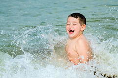 Child playing in surf at beach Stock Photo