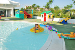 Child playing in swimming pool. Young girl playing in flotation device in swimming pool with toys in background, summer scene Stock Images