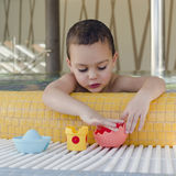 Child playing in swimming pool. Small child playing in a shallow children swimming pool with toys stock images