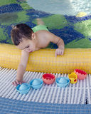 Child playing in swimming pool. Small child playing in a shallow children swimming pool with toys stock photo