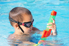 Child playing in swimming pool with water gun Stock Photos