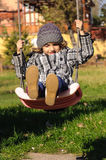 Child playing in swing Royalty Free Stock Photography