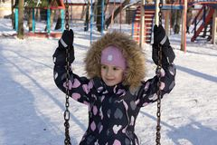 Child playing on a swing in winter.  On the nature.  Stock Photo