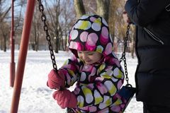 Child playing on a swing in winter.  On the nature.  Royalty Free Stock Photography