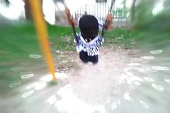 Child playing on swings stock footage