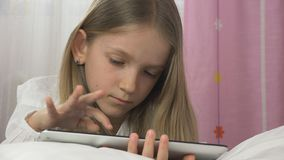 Child Playing Tablet in Bed, Kid Portrait Relaxing on PC, Not Sleeping Girl stock photo