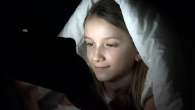 Child playing tablet in dark night, girl browsing internet in bed, not sleeping.  stock video footage