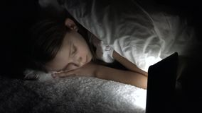 Child playing tablet in dark night, girl browsing internet in bed, not sleeping.  stock video