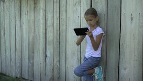 Child playing tablet by fence girl using smartphone outdoor children studying 4K stock footage