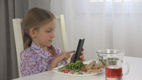 Child Playing Tablet, Kid Use Smartphone Eating Eggs, Salad Lettuce at Breakfast royalty free stock image