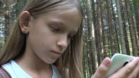 Child playing tablet outdoor in camping, kid use smartphone, lost girl in forest.  stock video