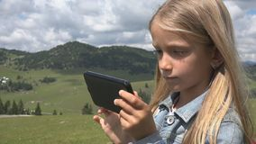 Child Playing Tablet Outdoor in Park, Kid use Smartphone on Meadow Girl in Grass royalty free stock photography