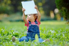 Child playing with tablet outdoors stock photography