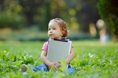 Child playing with tablet outdoors Royalty Free Stock Photo