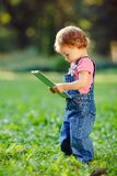 Child playing with tablet outdoors Royalty Free Stock Images