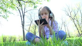 Child Playing Tablet in Park, Girl with Headphones on Grass Outdoor in Summer 4K stock video