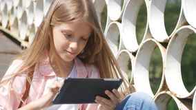 Child Playing Tablet in Park, Little Girl Uses Smartphones Outdoor in Nature stock video