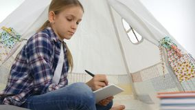 Child playing tablet in playroom girl writing homework for school kid playground.  stock footage