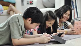 Asian boy and girl playing game on mobile phone together with smiling faces. Child playing with tablet or smartphone at home , Asian boy and girl playing game stock video footage