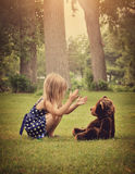 Child Playing with Teddy Bear Outside. A little girl is clapping her hands and playing with a teddy bear outside at a park for a friendship or imagination royalty free stock photos