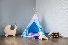 Child playing with a teepee royalty free stock photos