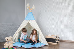 Child playing with a teepee tent. Child, preschooler kids, playing at home indoors with a teepee tent Royalty Free Stock Image