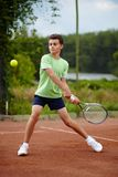 Child playing tennis. Child hitting the ball with the backhand on a dross court stock image