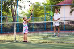 Child playing tennis on outdoor court Stock Photo