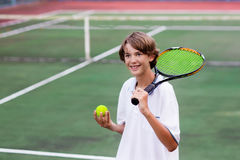 Child playing tennis on outdoor court Royalty Free Stock Images