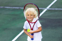 Child playing tennis on outdoor court. Little boy with tennis racket and ball in sport club. Active exercise for kids. Summer activities for children. Training Stock Image