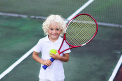 Child playing tennis on outdoor court Stock Images