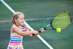 Child playing tennis on outdoor court Royalty Free Stock Image