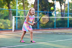 Child playing tennis on outdoor court. Little girl with tennis racket and ball in sport club. Active exercise for kids. Summer activities for children Royalty Free Stock Photo