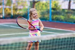 Child playing tennis on outdoor court Royalty Free Stock Photos
