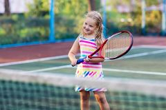Child playing tennis on outdoor court. Little girl with tennis racket and ball in sport club. Active exercise for kids. Summer activities for children Royalty Free Stock Images