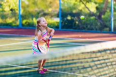 Child playing tennis on outdoor court Stock Photography