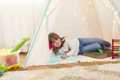 Child playing in a tent. Little girl playing in a tent in a play room stock photography
