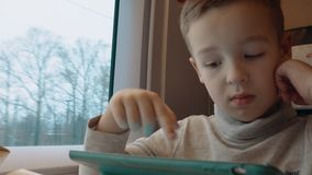 Child playing on touch pad during train ride. Boy traveling by train and entertaining himself with playing on digital tablet. Winter scene in the window stock video