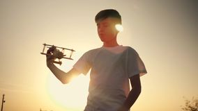 A child is playing with a toy airplane at sunset. Silhouette of a boy holding a toy, hand holding a small airplane. The. Child plays with a toy airplane in the stock video footage