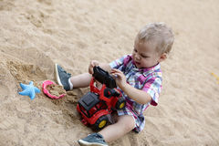 Child playing with toy bulldozer Stock Photo