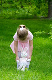 Child playing with a toy bunny in the garden Royalty Free Stock Image