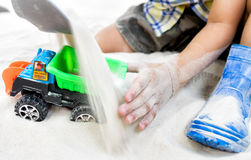 Child playing with toy car in sand playground. Stock Photography