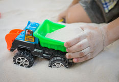 Child playing with toy car in a sand. Royalty Free Stock Image