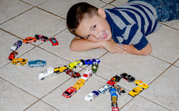 Child playing with toy cars spells out car Stock Image