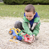 Child playing with  toy digger Stock Images