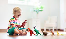 Child playing with toy dinosaurs. Kids toys. Child playing with colorful toy dinosaurs. Educational toys for kids. Little boy learning fossils and reptiles stock photo