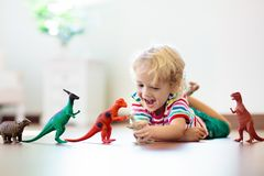 Child playing with toy dinosaurs. Kids toys. Child playing with colorful toy dinosaurs. Educational toys for kids. Little boy learning fossils and reptiles royalty free stock image