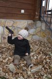 Child playing with toy gun. On the floor Royalty Free Stock Images